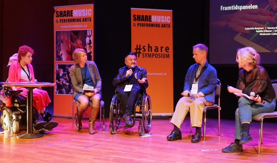 Five persons sitting on the stage. Behind them are orange rollups with photos of people dancing and the text ShareMusic & Performing Arts and #Sharesymposium.