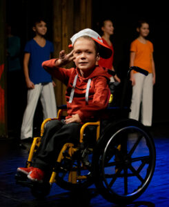 A young hiphop dancer in a red hoodie, a cap turned backwards, jeans and red sneakers. Hes sitting in a wheelchair with yellow details. Hes in the middle of a movement with his hand in a gesture before his eyes. Behind him there are three other children in bright colours. They also seem to be part of the dance, but the boy with red shoes is clearly the solo dancer.